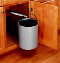 Also from Rev-A-Shelf is this pivot-out waste container with a lifting mechanism that raises the lid as the cabinet door opens and brings the container outside the door for access. The container features a built-in handle for easy removal. Minimum opening is 14 3/16 inches.