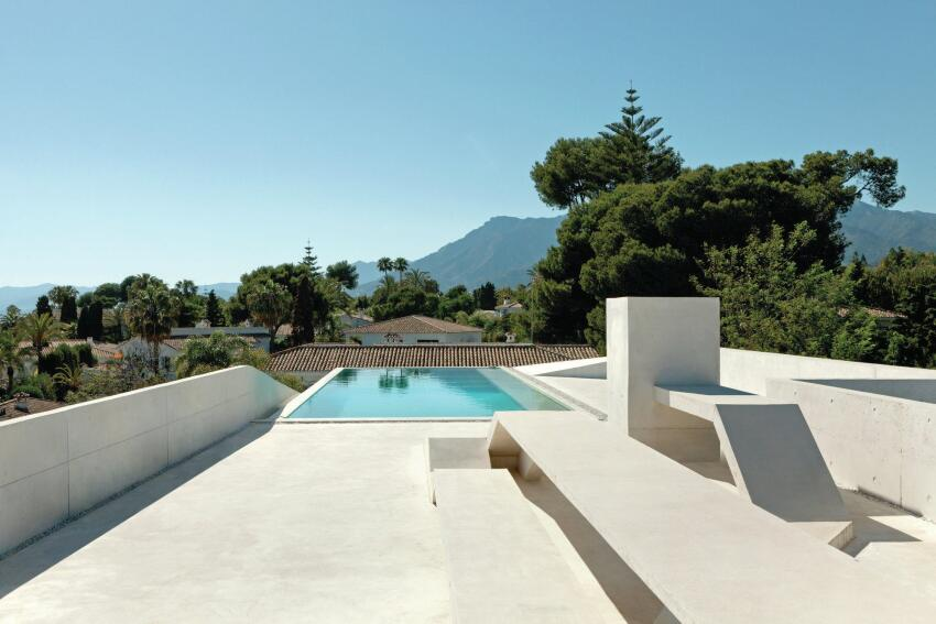 The rooftop pool deck features white concrete benches and views to the Mediterranean Sea beyond.
