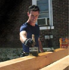 The author finishes rough-sawn cedar for a pergola, prior to assembly. That way, he can work on the ground; also, no surfaces are buried in joints and hidden from the brush.