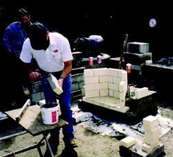 A thin layer of refractory mortar is placed on the firebrick with a small square  margin trowel.