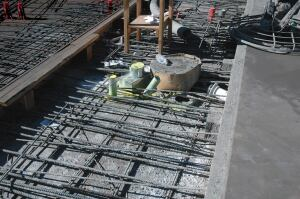 "This ""delay strip"" is cased in two locations for each deck of the Pelli Tower providing a place for shrinkage to occur. Post-tensioned reinforcement is tensioned here also. The strip is concreted after 21 days."
