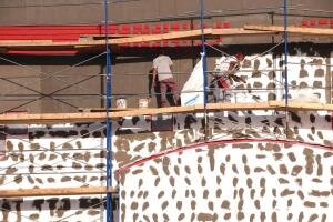 Workers stucco a new office building near the Huddlestons' house.