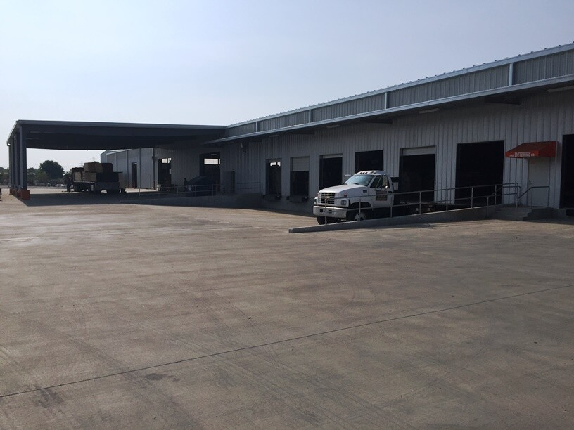 The warehouse includes multiple docks at truck and pickup truck height, along with a covered receiving area for all-weather operations.