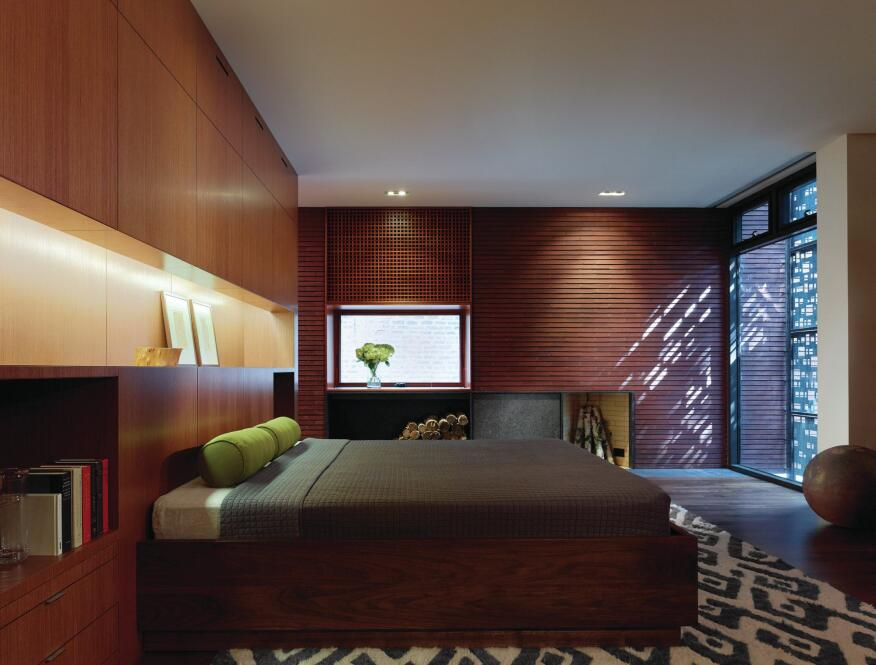 On the second floor, the master suite needs no curtains, as the perforated copper screen shields the street-facing windows.