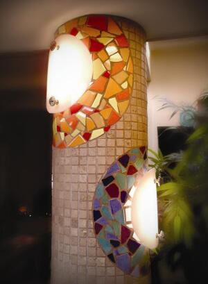 Arizona artist and remodeler Dana Ball made the covers for these light fixtures by heating circular pieces of Plexiglas in an oven and placing them on the cardboard Sonotube to fit the curve of the column. He used spacers to keep the covers at a consistent distance from the column. Drawer knobs that match those on the kitchen cabinets are used to secure the covers. The bolts for the knobs pierce the Sonotube and are secured with nuts to allow easy access for lightbulb replacement.