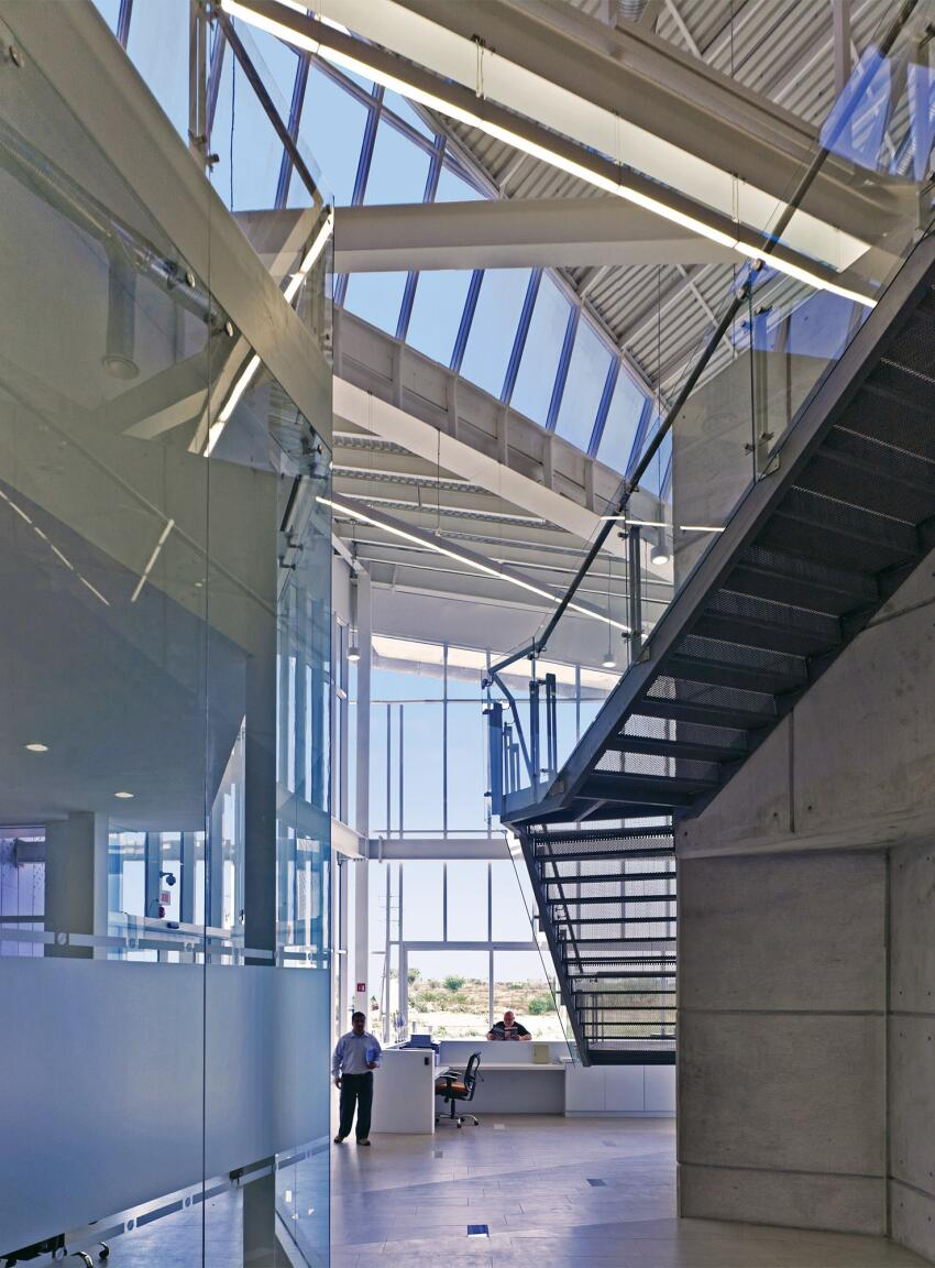 A metal stair leads from public areas for client meetings on the first floor to the proprietary research zones on the second.