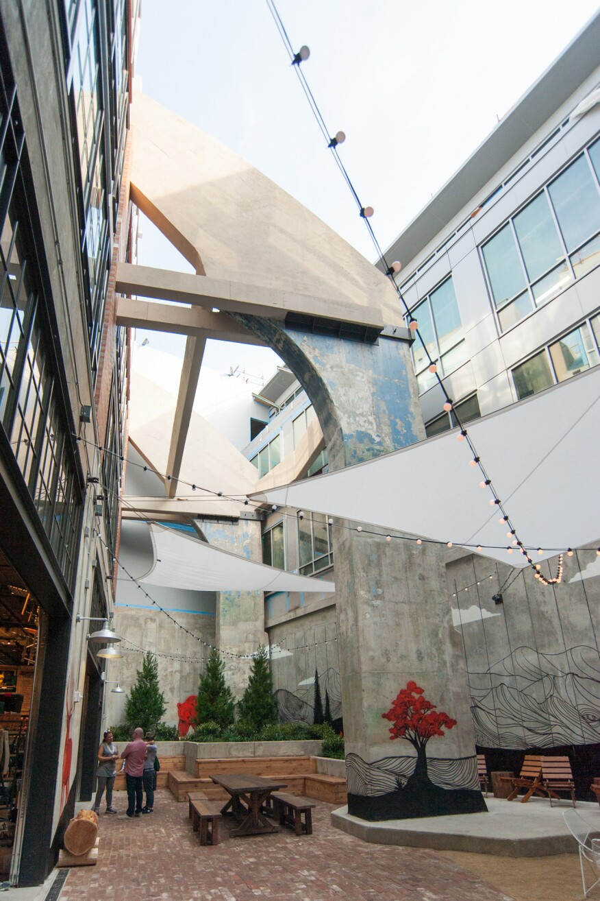 "The interior courtyard is the only space where visitors will experience the arena's full height. Created from a triangular wedge between the arena and the Ice House, the courtyard was hard fought by the design team because, business-wise, it's a non-selling area. An original flying buttress adds drama to the space while a mural by artist and rock climber Jeremy Collins with muralist Skye Walker celebrates the outdoors with an urban spin using spray paint on concrete. The design team didn't want to ""mimic the activity of where you're going to go"" with faux-realistic landscapes, Shapleigh says. ""It's already in our heads."" Today's gear stores don't need stylized ""lifestyle photos"" for marketing, Dowd says. ""That's what Instagram is for."""
