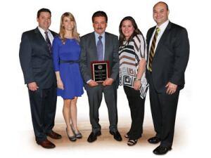 The Sanchez clan: Proudly  displaying a recent award are, l-r, Edgar Sanchez, COO; his wife  Julie; Cesareo Sanchez, president; Karla (Sanchez) Escobar,  director human resources; Al Escobar, sales/marketing  manager.