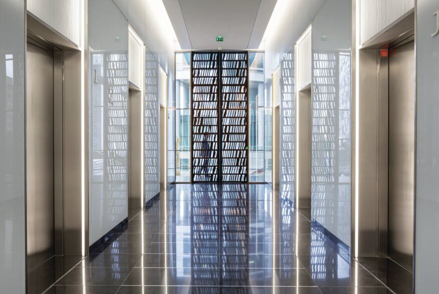 The elevator banks feature decorative metal doors that open out on circulation spaces lined in panels from Rheinzink.