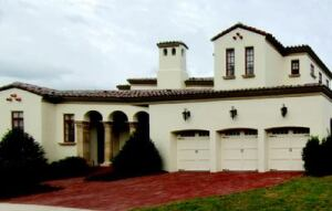 """ON THE SIDE: Garage facades can sometims appear monolithic, but not this one.  Attractive second-story massing and an adjacent first-floor loggia downplay the auto focus of the InSync Home's utilitarian side.  Quaint lighting fixtures, carriage-style doors, variegated concrete pavers, and a 4/12 -pitch """"boosted"""" barrel tile roof by MonierLifetile add flavor to the home's Spanish eclectic vernacular."""