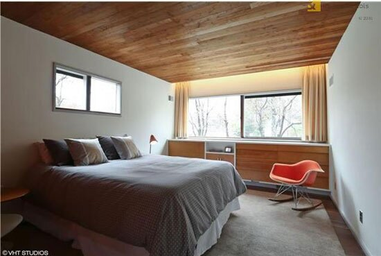A bedroom in the Snower Residence with Breuer's signature sliding windows and an Eames Rocking Chair (right.)