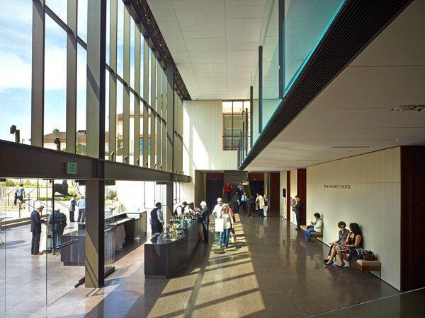 The Bram Goldsmith Theater lobby overlooks a terraced courtyard through a west-facing window wall.