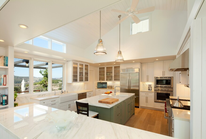 This all-white kitchen keeps a large room simple with clean, modern lines. Frosted glass cabinet doors and marble countertops add dimension to the white color scheme, while skylights in the angled ceiling provide a flood of natural light that opens up the space.Project: Arroyo Grande Modern Farmhouse by Gast Architects