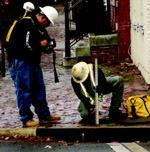 A Woolpert surveyor takes measurements and determines pipe sizes on a section of the sanitary sewer system in Alexandria's Old Town historic district. Attribute data was collected for both pipes and manholes—approximately 20 attributes per structure.