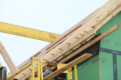 The subfascia fits into the notch cut into the rafters, and the soffit ledger attaches to the wall over a layer of 30-lb. felt paper.