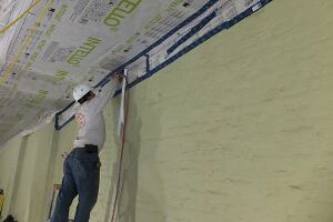 "A worker staples ProClima Intello ""smart"" vapor control membrane to the underside of the building's roof framing. After the membrane is taped to the coated party walls, the air-tight envelope will be continuous—hopefully enabling the building to meet the Passive House specification (see slideshow, ""Old School Meets High Tech: Air-Sealing a Brick Row House"")."