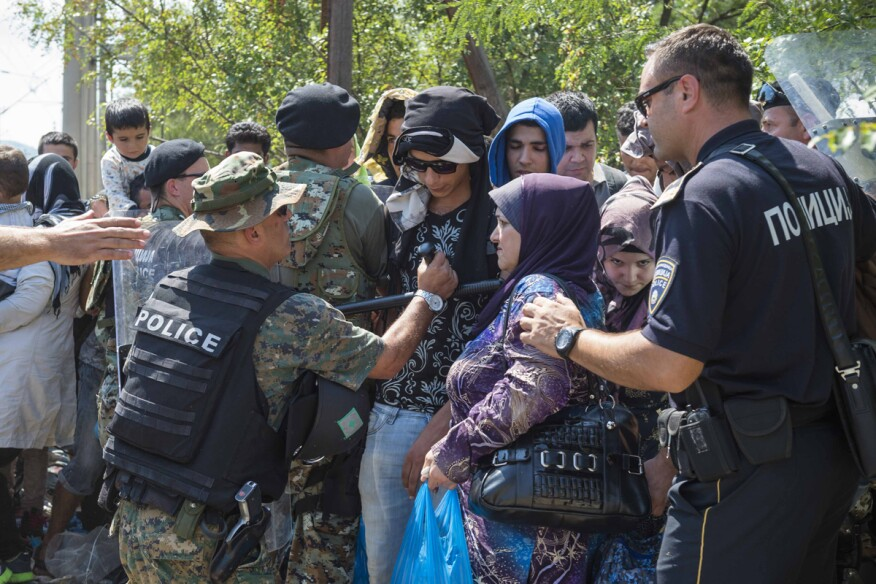 Syrian refugees entered Macedonia from Greece after police allowed them to pass despite earlier trying to hold back the crowd using stun grenades.