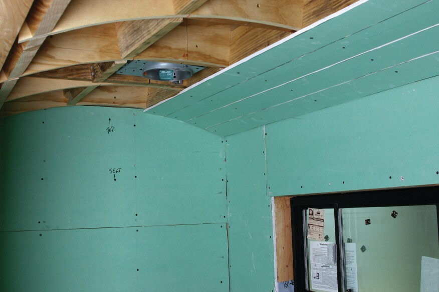 To shed water properly, bathroom ceilings should never be flat. Here the ceiling is arched and a tight grid has been framed to support the tile. Strips of green board form the initial arched surface.
