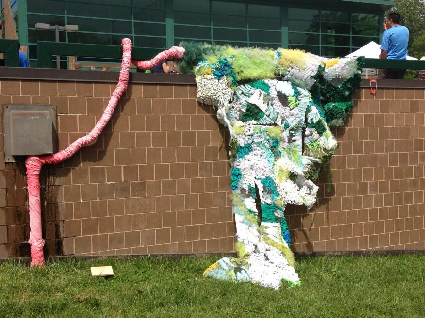 """Drain Tree For this installation, the students chose a drain on the outer wall of the library complex that had been broken and leaking for some time. The idea was to """"create something really alien coming out of the drain, Fox says, to showcase that """"cool things can happen when you try to fix something yourself."""" The students gathered materials such as t-shirts, table cloths, """"anything that was a shade of green,"""" Fox says, and wove it together to form an organic mass emerging from the broken drain. Students and residents were then writing notes about changes they would like to see in the community and pinning it to the installation in an effort at community engagement. As a side note: part of the efforts to clean up the plaza and surrounding environs before the installations were put in place reportedly included fixing the broken drain that inspired the project."""