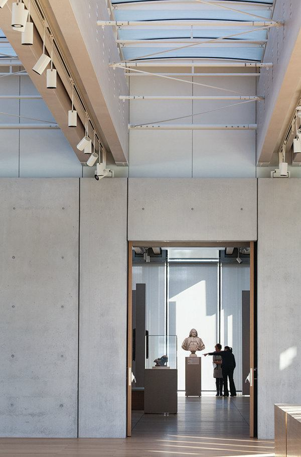 LED spotlights are suspended from tracks positioned in between the wood beams. The structure and lighting assembly continue through to the galleries beyond.