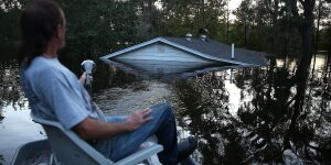ANDREWS, SC - OCTOBER 08: Buddy Benford pilots his boat past a home nearly submerged by flood water coming from the breached dams upstream as the water continues to reach areas in the eastern part of the state on October 8, 2015 in Andrews, South Carolina.  The state of South Carolina experienced record rainfall amounts over the weekend and officials expect the damage from the flooding waters to be in the billions of dollars.  (Photo by Joe Raedle/Getty Images)