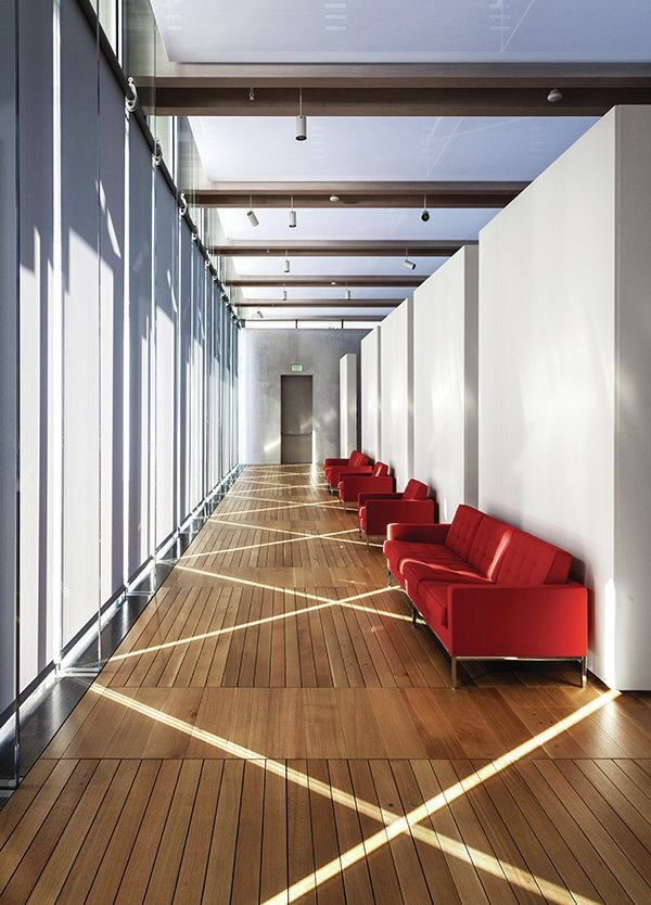 Red couches are placed behind the movable exhibition walls in the south gallery. View to the west.