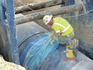 A worker prepares to install a shrink sleeve over the pipe joint to keep dirt and rock away from the connection as the trench is backfilled. Welding then occurs underground within the buried pipe.