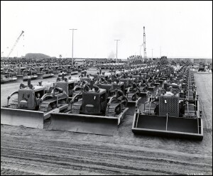 Figure 01. The Allies would deploy more than 100,000 tractors during World War II. Earthmoving equipment manufacturers like Caterpillar, International Harvester, Allis-Chalmers, and LeTourneau provided the mechanical muscle behind the land-clearing and construction efforts of Army Corps of Engineers in Europe and the Naval Construction Battalions (NCBs) or Seabees in the Pacific. In this photograph from 1944, International Harvester TD-9 crawler tractors equipped with bulldozer blades and front-end loaders are lined up in large groups in preparation to be shipped to various Pacific battle zones.