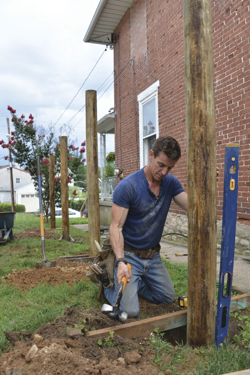 The author hammered pairs of 2x4 stretchers into the ground to temporarily hold the plumbed 6-inch-diameter PT posts in position while pouring concrete around the post bases. The post holes are 36 inches deep, or frost depth.