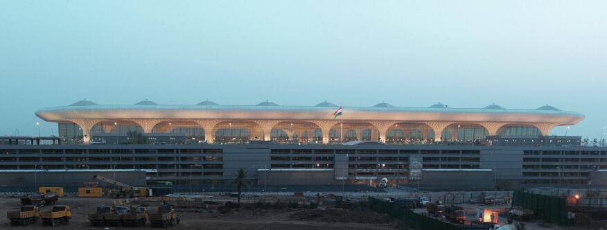 The airport's long-span steel structure is supported by a grid of composite mega-columns that comprise a 2.3-meter-square cruciform steel structure encased in a 2.7-meter-diameter concrete casing. The panels attach to the structure with a system of aircraft wire and steel hooks molded into the glass-fiber-reinforced gypsum and concrete.