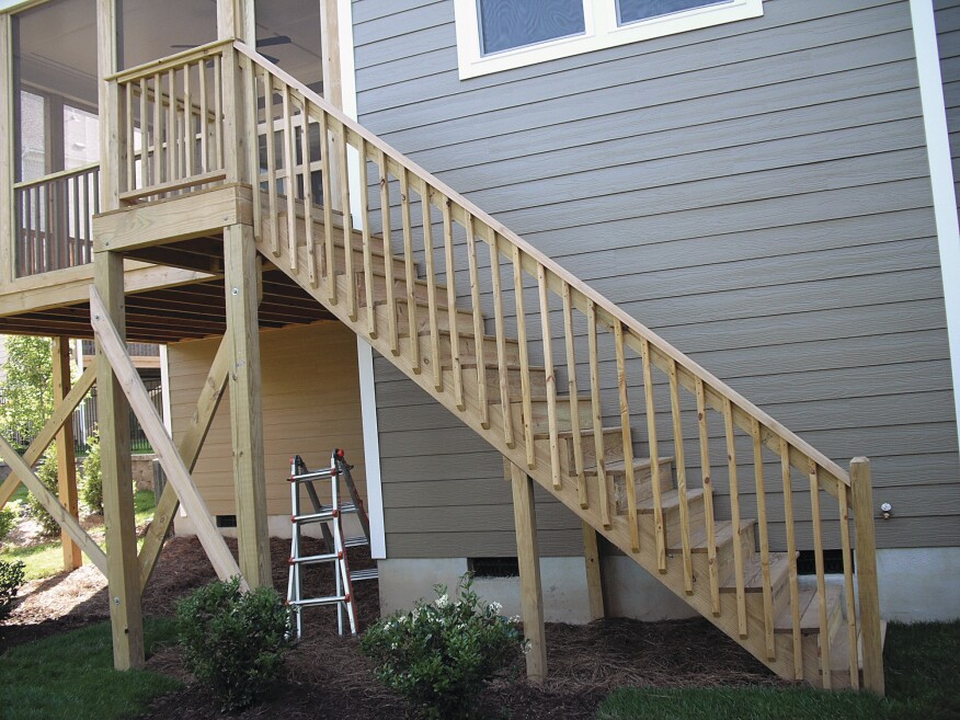 Stair guard posts should be located so that the span between posts (as measured horizontally) is no more than 6 feet. This is a photo of a new deck that has passed inspection.