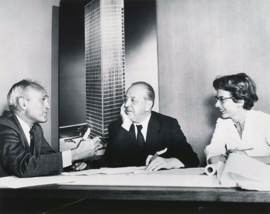 Philip Johnson, Ludwig Mies van Der Rohe, and Phyllis Lambert discuss the Seagram in front of an image of the building model soon after she helped the architects win the commission in 1955.