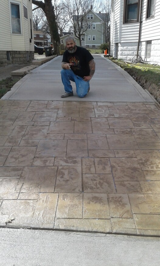 Victor Addis posing with the finished driveway and stamp work. He screeded the entire front half, finished the edges, cut the joints, hustled to the stamp area, applied the color, and did the stamping.
