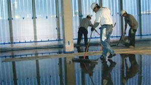 Compared to finishing other concrete placements, self-leveling overlays are easy. The worker shown here uses a smoothing trowel (which resembles a large squeegee) to quickly pass over the plastic concrete.