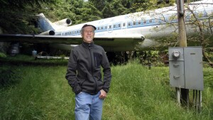 Bruce Campbell stands near his Boeing 727 home in the woods outside the suburbs of Portland, Oregon May 21, 2014. In 1999, the former electrical engineer had a vision: To save retired jetliners from becoming scrap metal by reusing them. Campbell, 64, is one of a small number of people worldwide who have transformed retired aircraft into a living space or other creative project, although a spokesman for the Aircraft Fleet Recycling Association was unable to say precisely how many planes are re-used this way. Picture taken May 21.  REUTERS/Steve Dipaola  (UNITED STATES - Tags: SOCIETY TRANSPORT REAL ESTATE) - RTR3SP8I