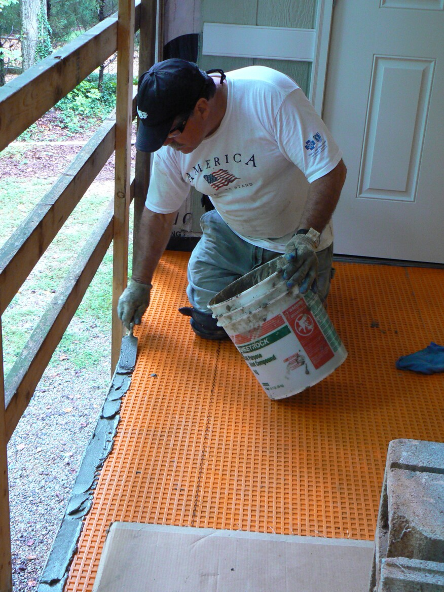 To finish the open edge of the porch, the author installed Shluter's  Rondec-Step metal trim, first spreading a bed of thinset over the membrane.
