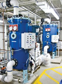 Designed for demand: Though many  components of a large commercial equipment room are just scaled-up  versions of their residential cousins, some — like these  regenerative media filters — are specially engineered to  handle huge gallonages and bather loads.