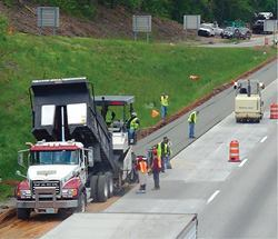 Concrete may fast become the budget-friendly material of choice for road-building and paving. Here crews place roller compacted concrete on a freeway shoulder. Photo: Portland Cement Association