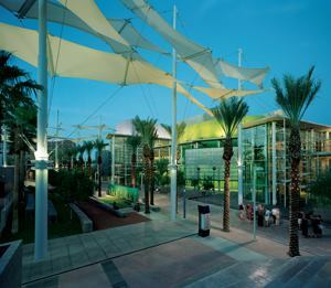 Fabric canopies standing approximately 50 feet tall stretch along the Shadow Walk plaza. Providing shade along the walkways during the day, at night the canopies are illuminated with 48W fluorescent uplights and 24W compact fluorescent downlights. Each canopy mast has three uplight and three downlight fixtures.