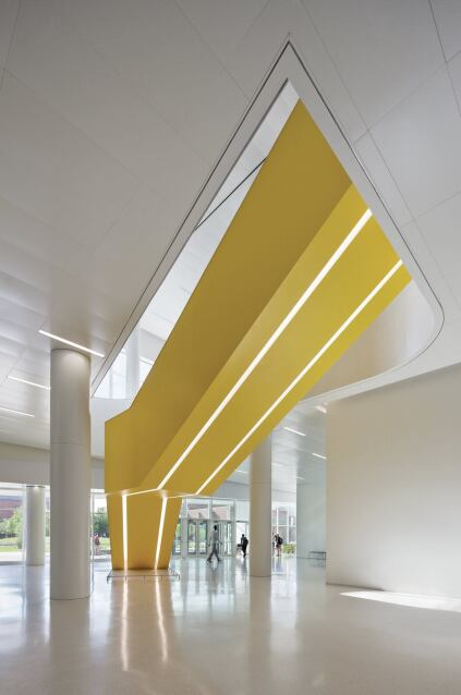 Yellow stairways, such as this one leading from the ground-floor entrance to the main lobby, incorporate light fixtures on their undersides.