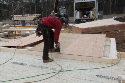 The sheathing for this house had to be installed according to an engineered plan for high-wind considerations. Here the corners of the plywood sheets are tacked to the frame.