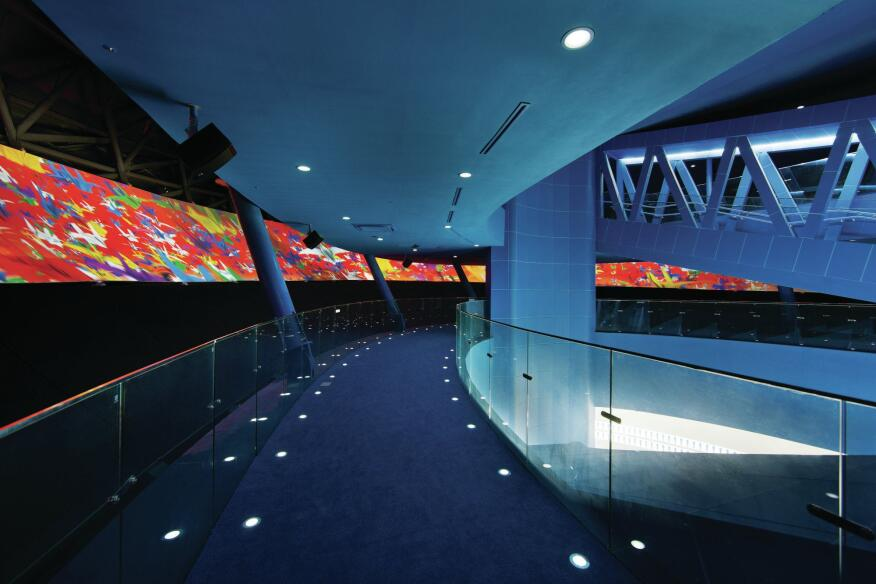 "The main exhibition floor's sweeping interior walls host large-scale digital projections, and the open stair that cuts through the space gives visitors different vantage points for viewing the animated multimedia events. Images cascade across streamlined exhibition screens, and are paired with matching auditory environments. The themes for the displays have their roots in the Four Rivers Project, where themes of ""happiness,"" ""culture,"" ""economy,"" and ""ecology"" distinguish the different sections of the project. ""One of the questions we asked ourselves in conceptualizing the ARC was 'How do we offer an architectural entity that meets the expectations of today's technology?' "" Rashid says. ""Our solution was to load the structure with absolute technological potential in order to allow it to be a canvas that both communicates with and reacts to its occupants in a way that reflects the human condition."""