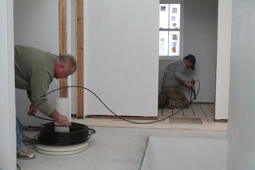 To install the tubing, one person uncoils it while another presses it into the grooves with a soft hammer handle. Occasionally, a block has to be used to seat the tubing properly.