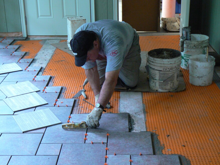 The porcelain tile used to finish the floor was applied in a pinwheel pattern, which requires two different sizes of square tiles. Usually (but not always) one tile in this pattern is twice as big as the other. In this case, the large tile was 11 3/4 inches square and the small tile was 5 3/4 inches square. With a 1/4-inch mortar joint, the size of the increments for the layout ended up an even 12 inches and 6 inches.