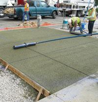 A crew adds decorative joints to gold-colored pervious concrete.