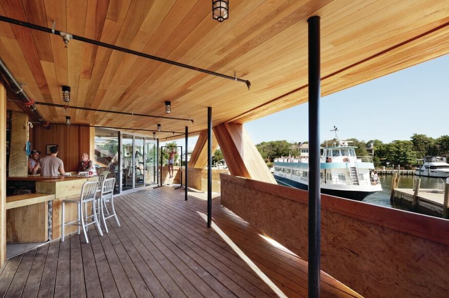 The first-floor terrace, with its outdoor bar, is lined with cedar on the floor, ceiling, and walls. A glass-enclosed gym overlooks the harbor.