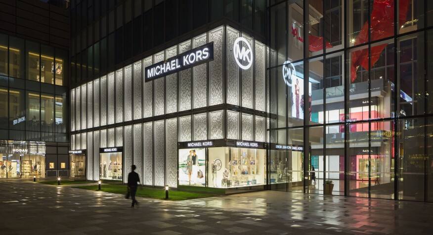 The facade of the Michael Kors Shanghai flagship store illuminated at night.