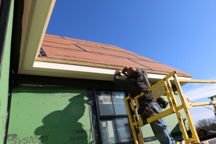 The crew nails the fascia in place. The dado creates a consistent reveal and shadow line along the edge of the cornice.