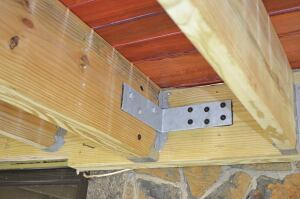 On a second-story deck, a building inspector may accept galvanized L-brackets fabricated from 1/4-inch steel and attached to the deck framing and house framing with structural screws as shown, in lieu of the threaded-rod hold-down anchors contained in the IRC.