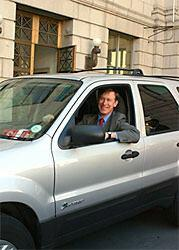 """Colorado Gov. John W. Hickenlooper, former Denver mayor, in his """"official vehicle,"""" a Ford Escape SUV, one of more than 130 hybrid-electric vehicles in the city's Green Fleet program. Expanding the fleet of ecologically friendly cars is one goal of Greenprint Denver."""